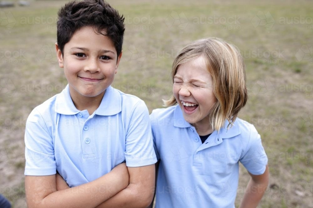 Smiling boy and girl standing outside wearing school unifom - Australian Stock Image