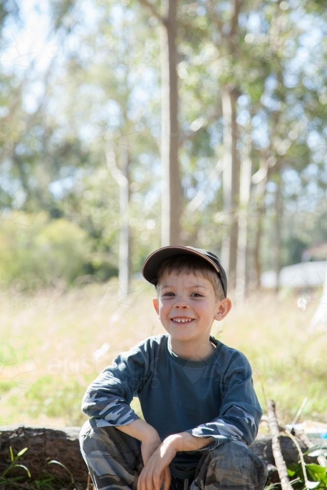Smiling boy sitting on a log in a paddock by a campfire - Australian Stock Image