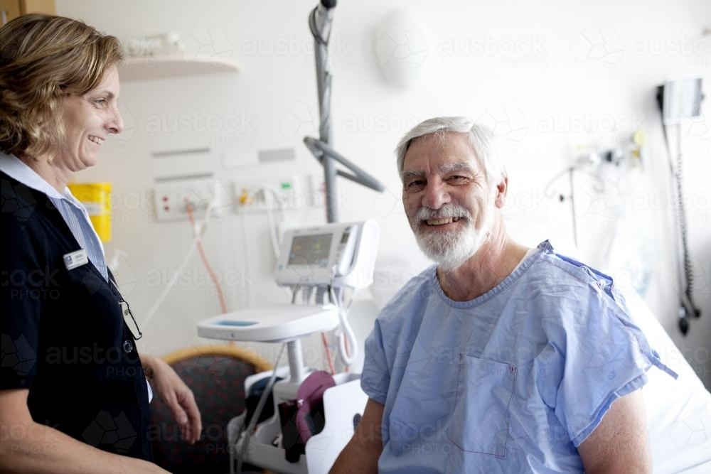 Smiling middle aged male patient being treated by a nurse in a hospital ward - Australian Stock Image
