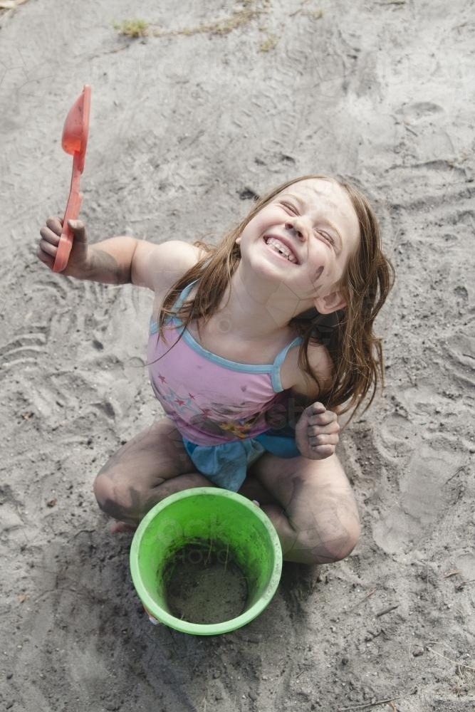 Smiling young girl playing in dirt with a bucket and spade - Australian Stock Image