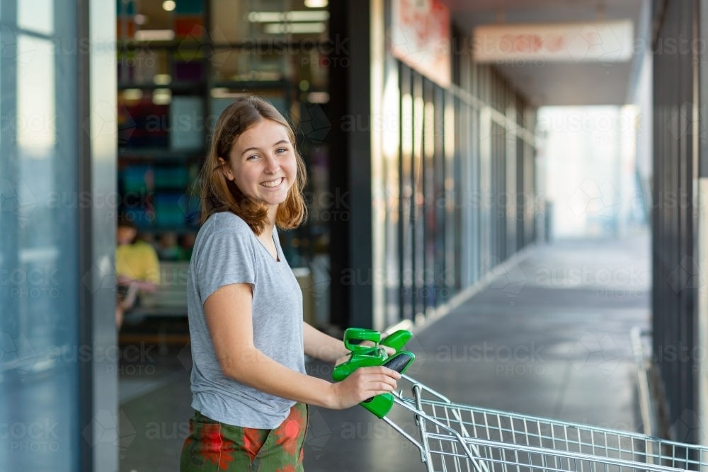 smiling young woman pushing shopping trolley at shops - Australian Stock Image