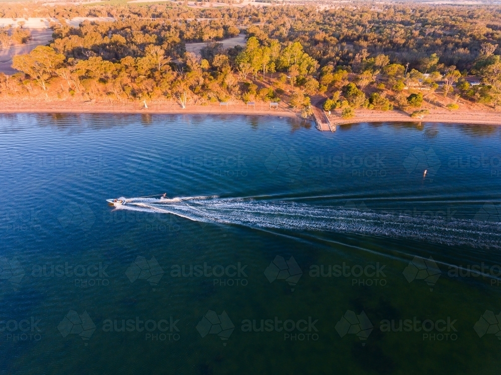 speedboat towing skier on Lake Towerrinning with land in background - Australian Stock Image