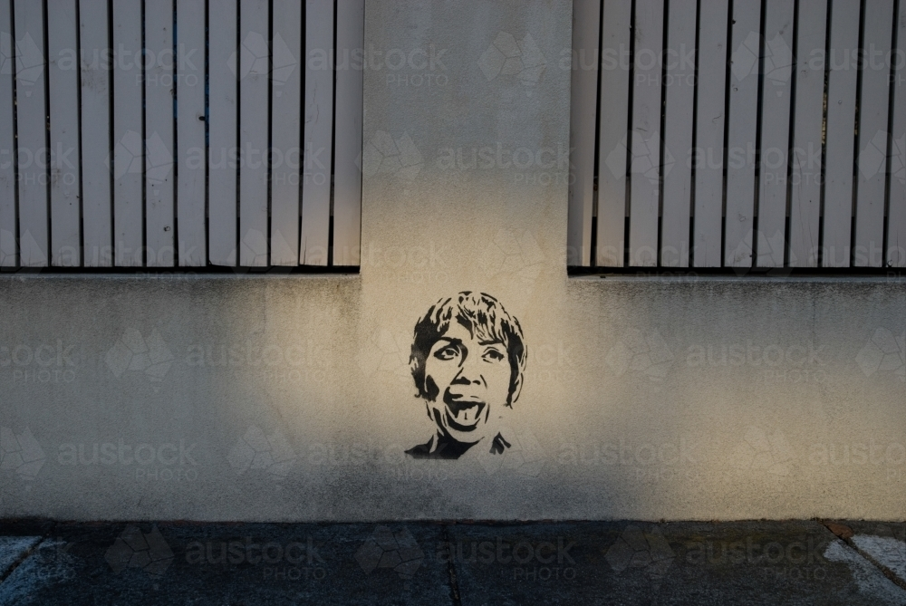 Stencil graffiti of a woman with short hair who is singing or shouting