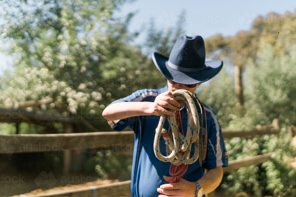Stockman with Blue Hat Winding a Rope - Australian Stock Image