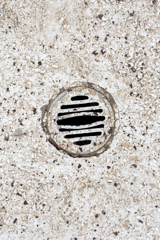 Stone floor with water drain in public toilet - Australian Stock Image