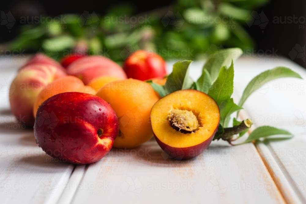 stone fruits on a wooden white background - Australian Stock Image