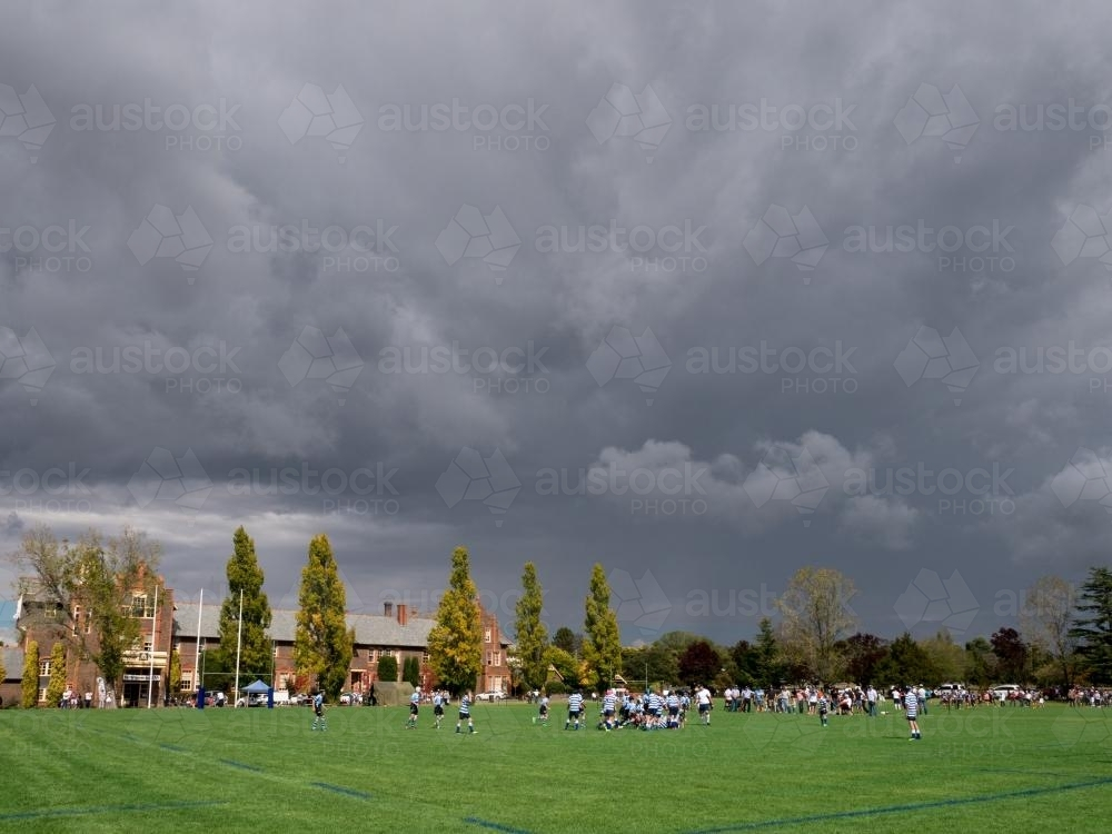 Storm clouds over a football match at The Armidale School - Australian Stock Image