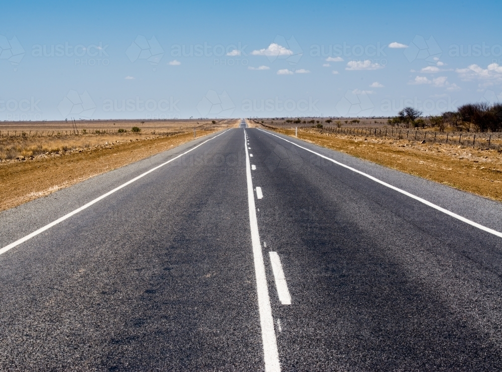 Straight bitumen road with white lines to horizon through drought stricken flat country - Australian Stock Image