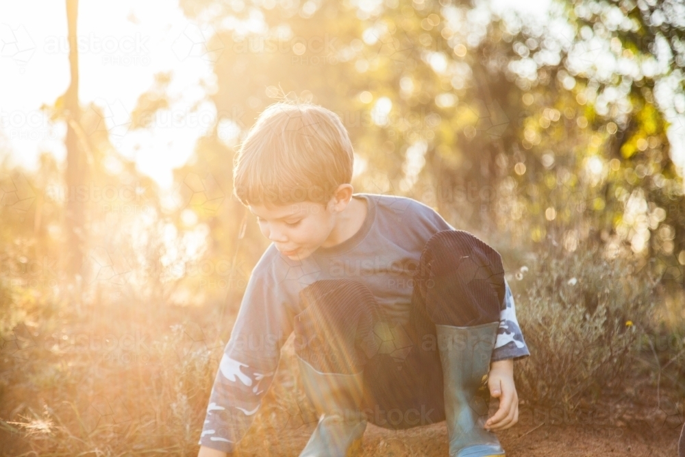 Sun flare over child playing in the dirt - Australian Stock Image