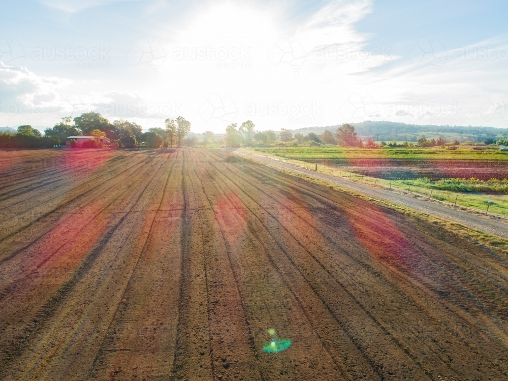 Sun flare over farm paddock with soil ready for planting - Australian Stock Image