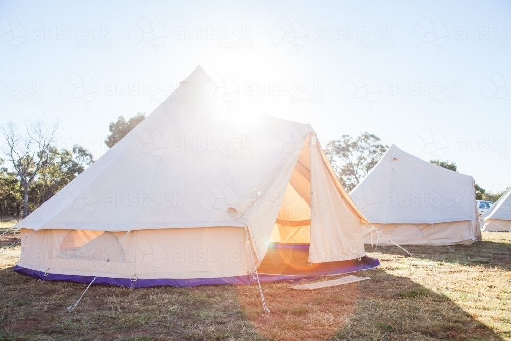 Sun flare over huge white tent with open flaps in the morning - Australian Stock Image