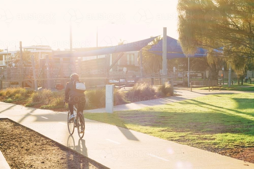 Sun haze over cyclist riding on a bike path in Brighton - Australian Stock Image