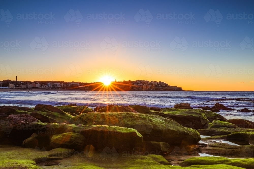 Sun rising over moss covered rocks along coastline with blue sky - Australian Stock Image