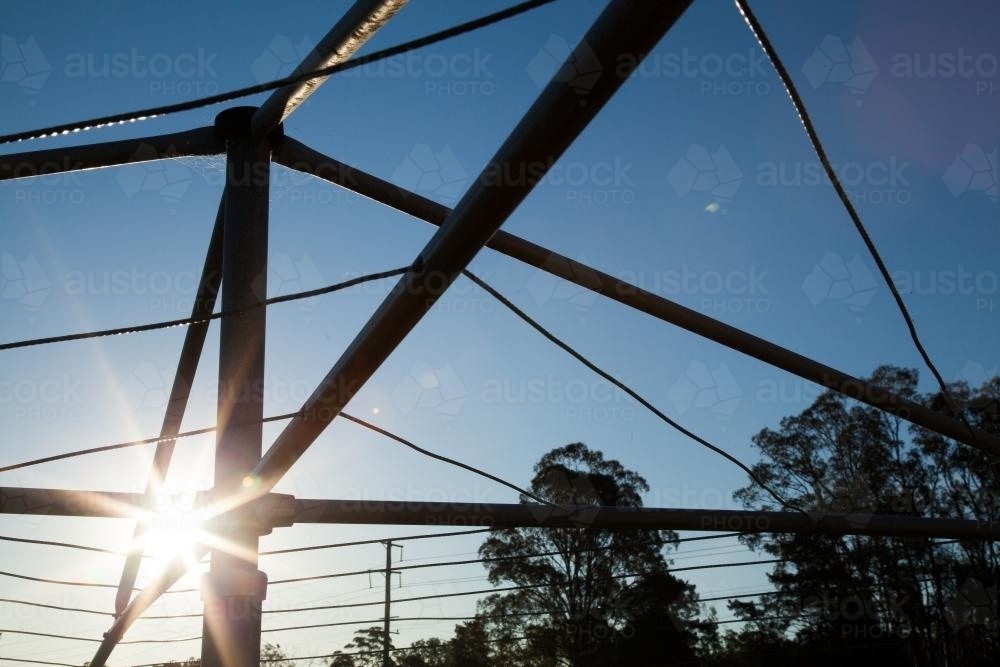 Sunlight shining through a hills hoist washing line silhouetted against sky - Australian Stock Image