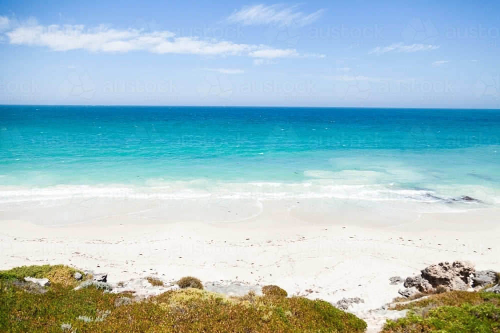 Sunlit coastland with view of shrubs, beach and clear blue coastal waters - Australian Stock Image