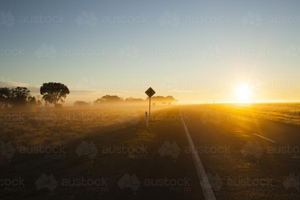 Sunrise on a  regional highway with silhouette road side sign - Australian Stock Image