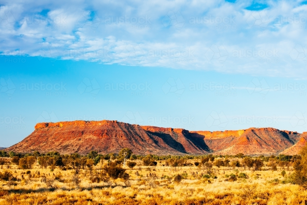 Sunset colours on the rising landforms above the plains near Kings Canyon in Central Australia - Australian Stock Image
