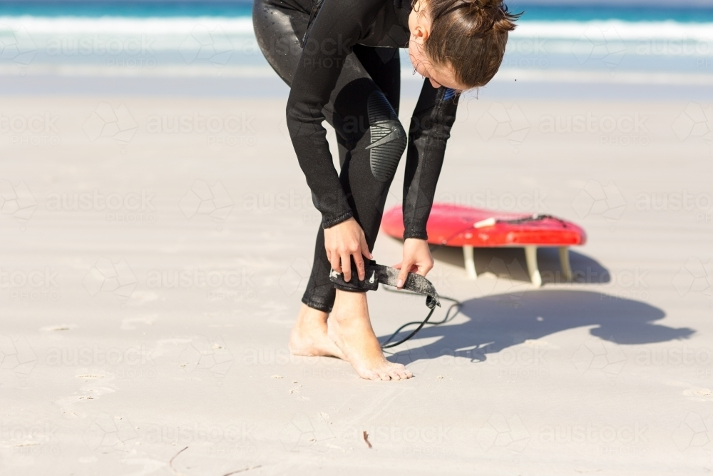 Surfer fastening leg rope on white sand beach - Australian Stock Image