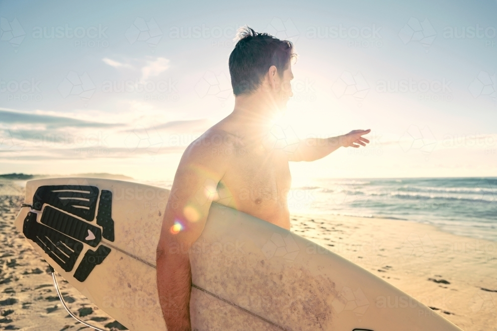 Surfer pointing to the ocean - Australian Stock Image
