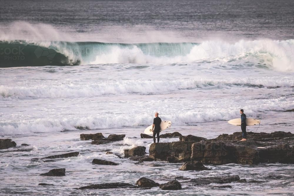 surfers getting ready to enter the ocean from rocks - Australian Stock Image