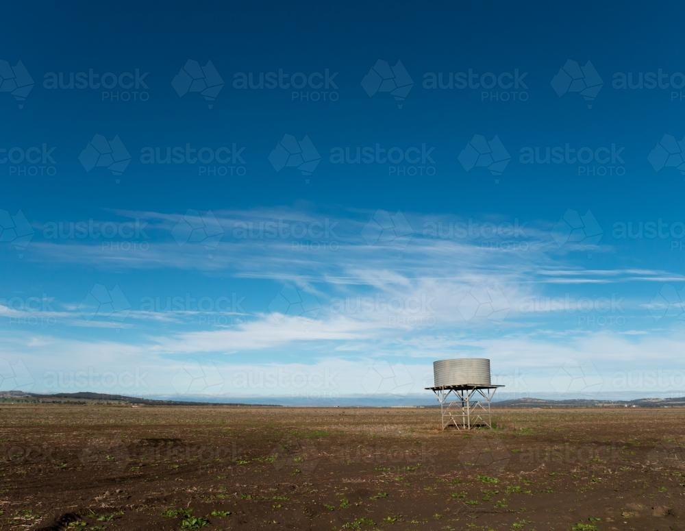 Tank stand in a treeless paddock against blue sky - Australian Stock Image