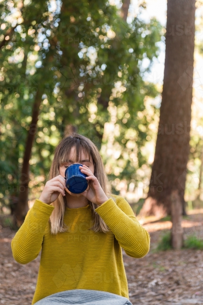teen girl drinking from a mug on a picnic in the forest - Australian Stock Image