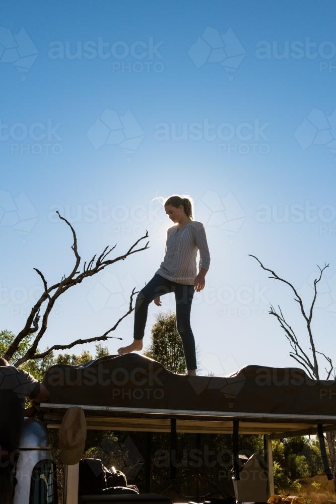 Teen girl helping pack up the roof top tent, from a camping road trip - Australian Stock Image