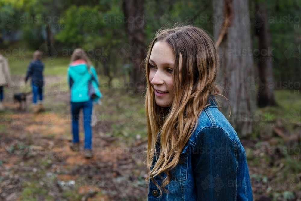 teen girl lagging behind a group of kids in a forest - Australian Stock Image