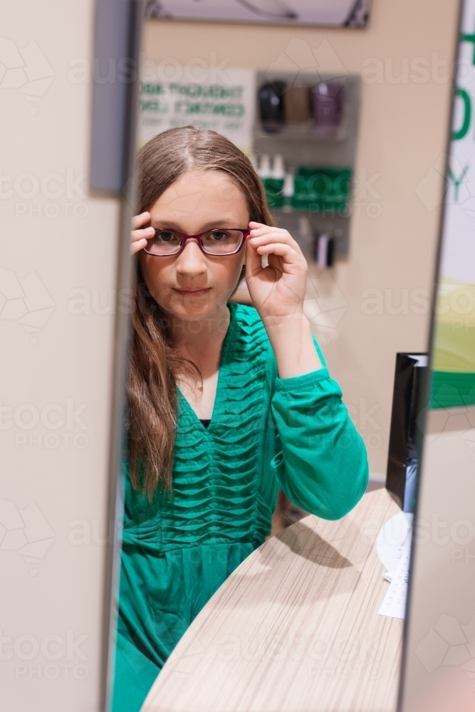 Image of teen girl trying on new glasses, looking in the