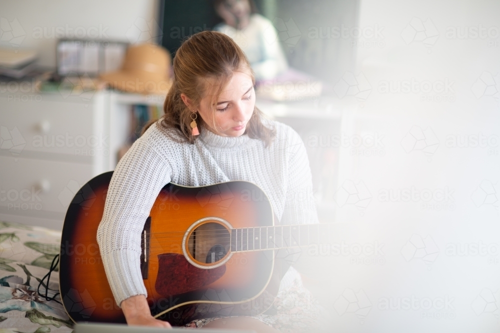 Teen learning guitar partly obscured by curtain - Australian Stock Image