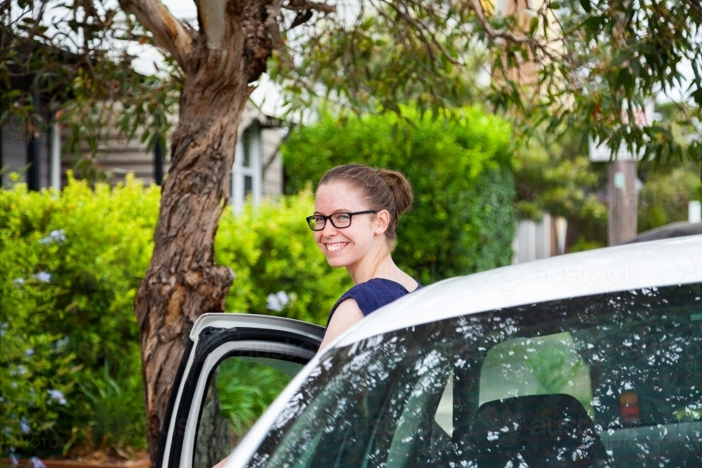 Teen person getting into passenger seat of car - Australian Stock Image