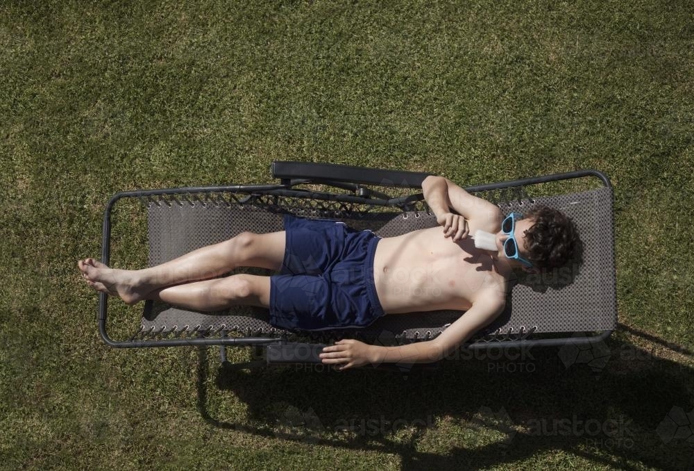 Teenage boy eating icypole while sunbaking - Australian Stock Image