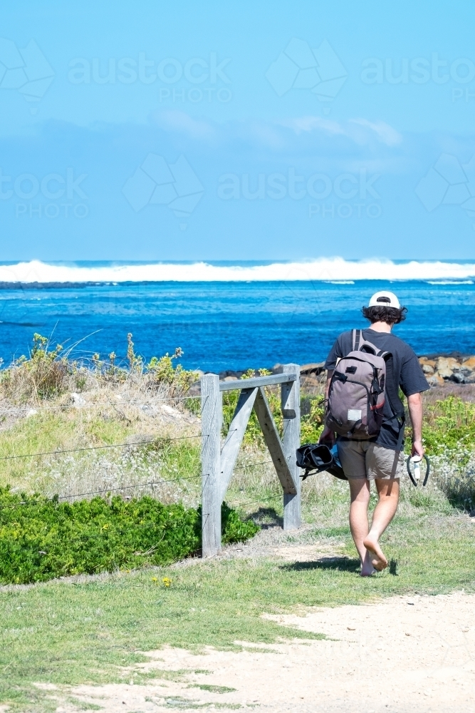 Teenage boy heading off for a snorkel at the beach - Australian Stock Image