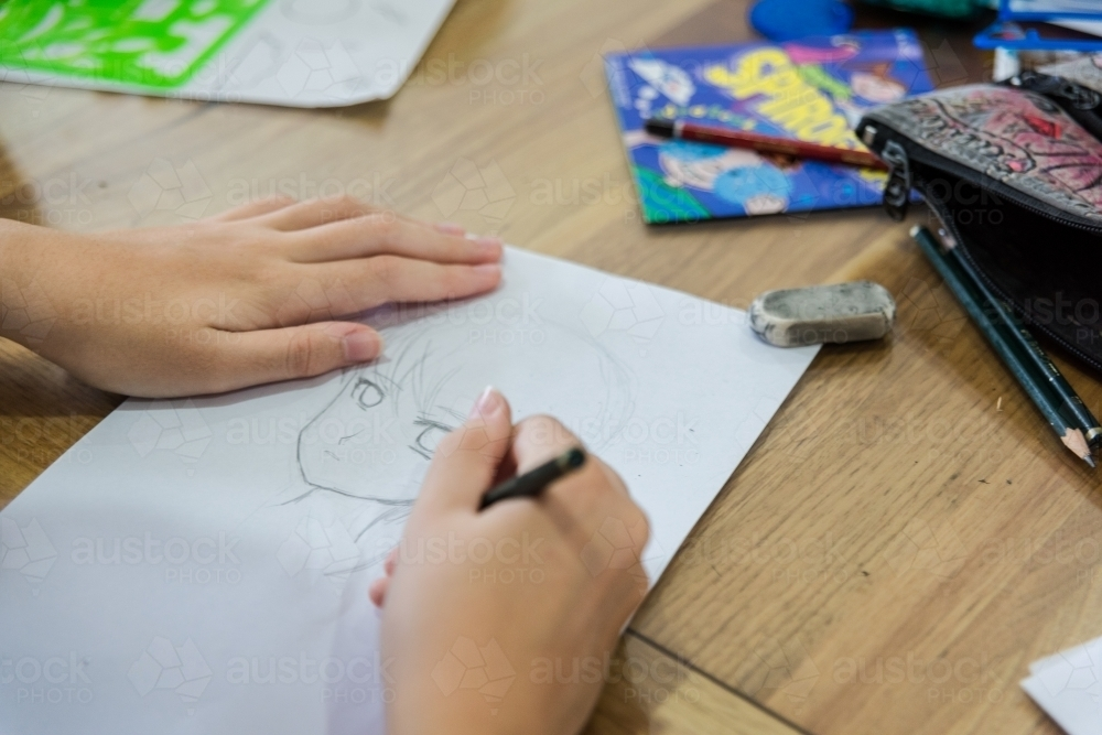 Teenage girl drawing Manga artwork at the table - Australian Stock Image
