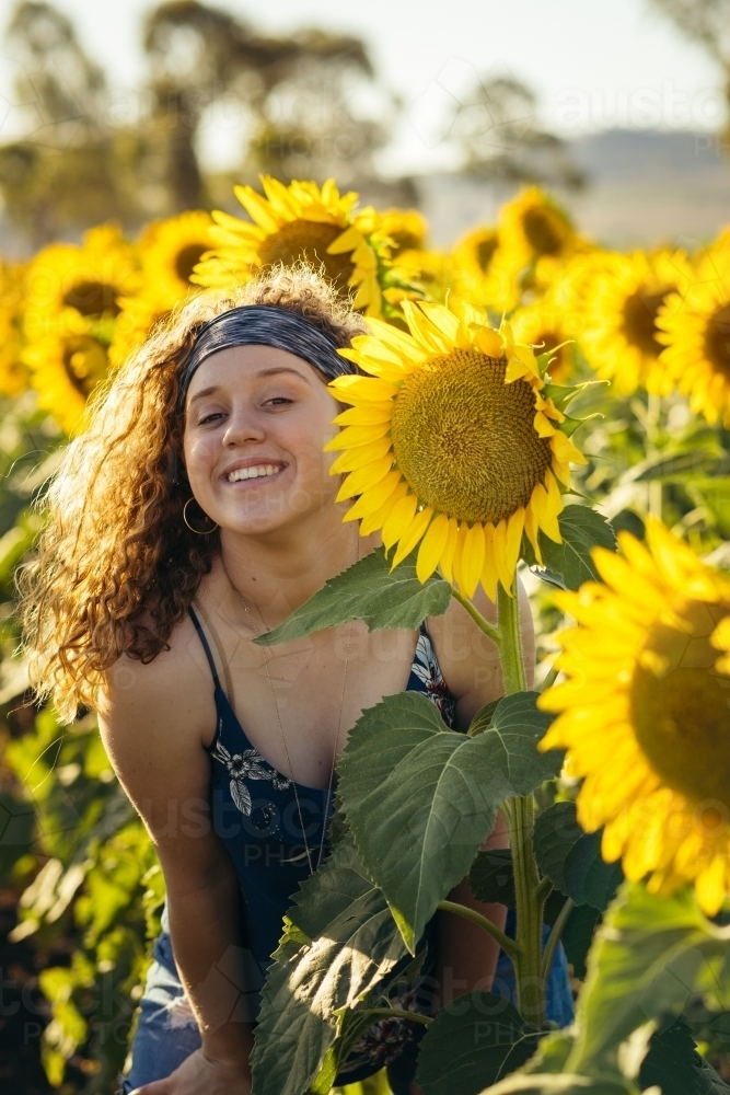 Teenage girl smiling in sunflower field - Australian Stock Image