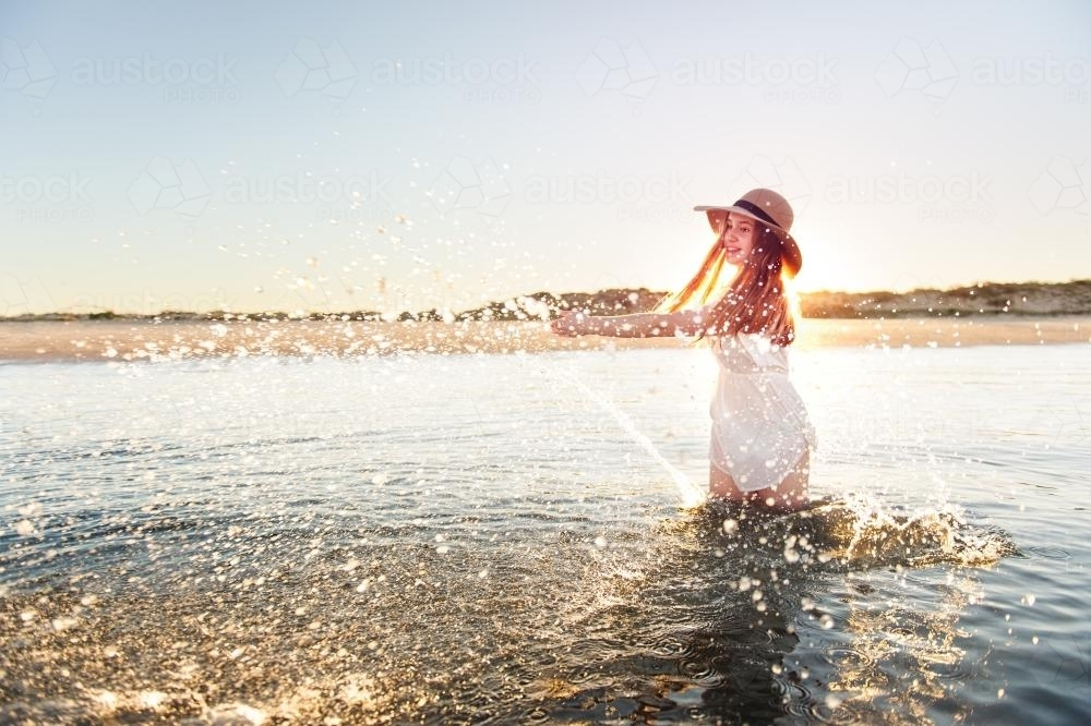 Teenage girl splashing water at the beach with the setting sun behind her - Australian Stock Image
