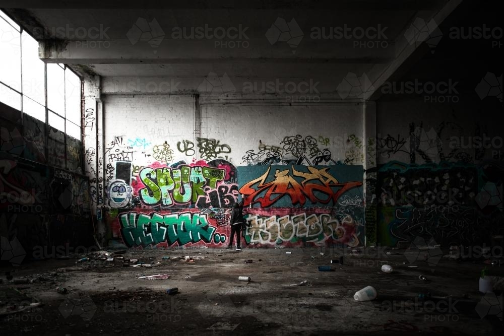 Teenage graffiti artist spray painting a wall in disused warehouse - Australian Stock Image