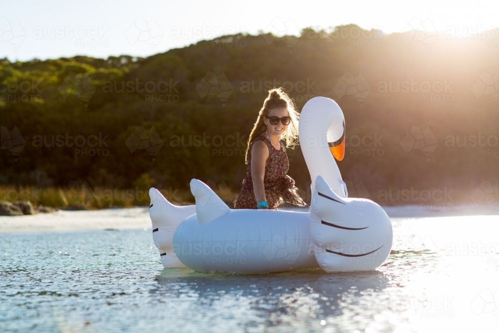 Teenager in the water with a giant inflatable swan