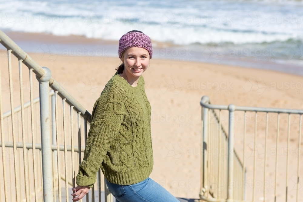 Teenager in warm clothes on steps to beach - Australian Stock Image