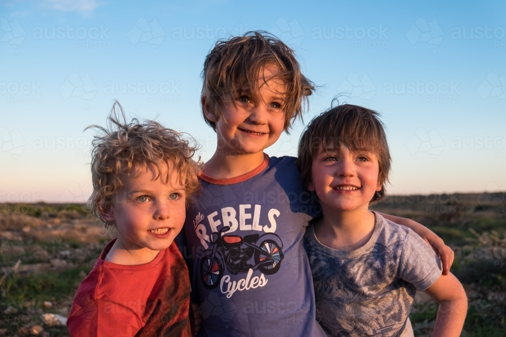Three boys embracing at sunset - Australian Stock Image