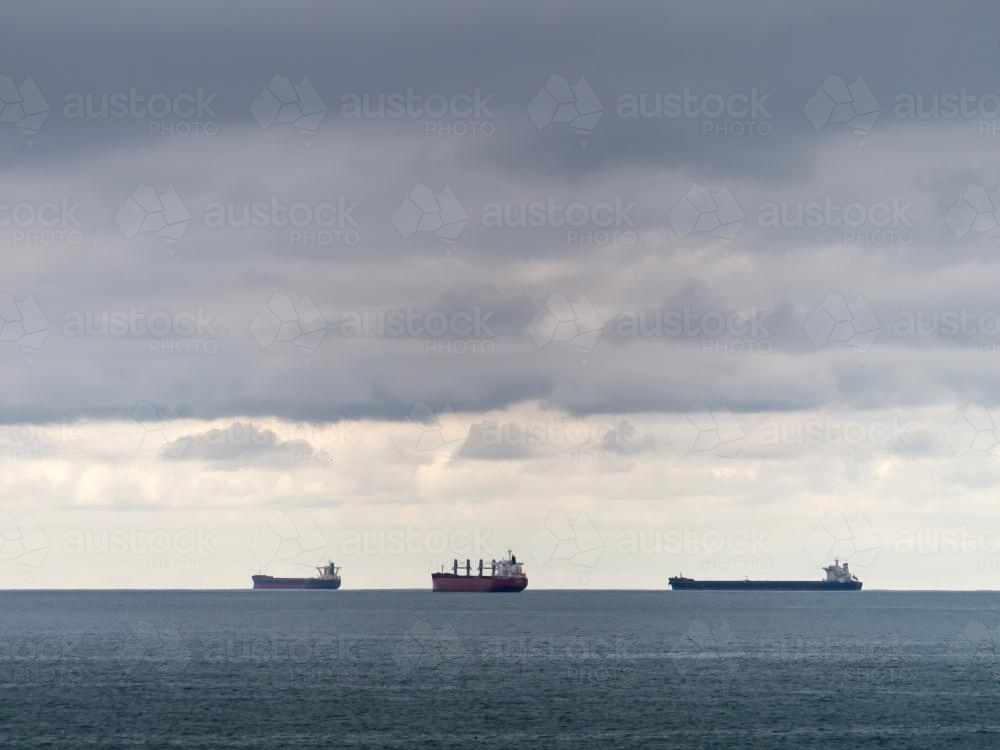 Three bulk carriers on the horizon on a cloudy day - Australian Stock Image