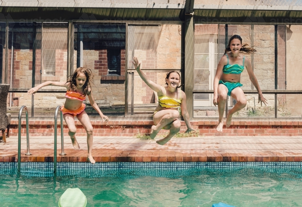 Three girls jumping into a swimming pool - Australian Stock Image