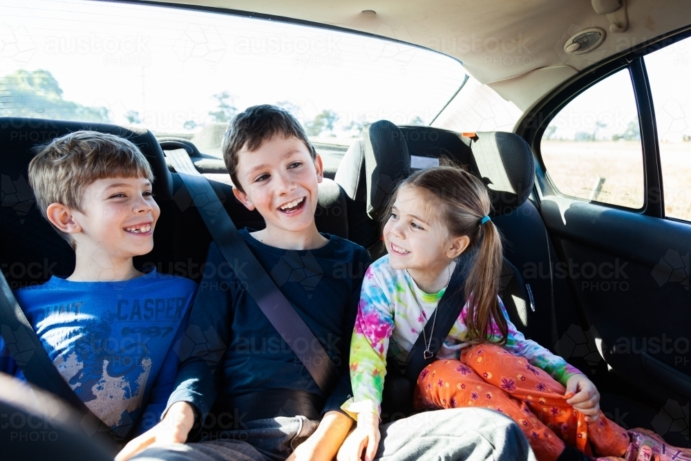 Three happy siblings in the back of a car - Australian Stock Image
