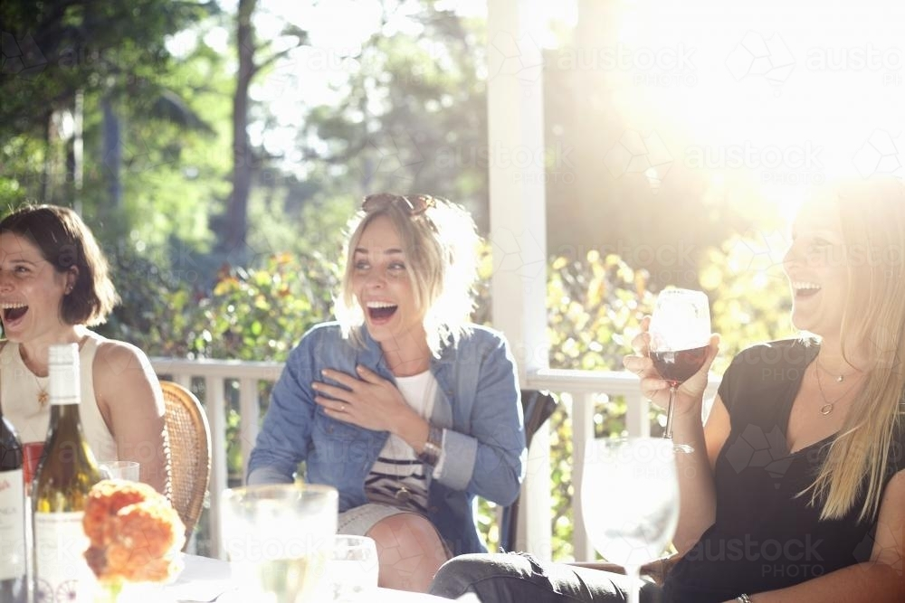 Three laughing women sitting on verandah having drinks - Australian Stock Image