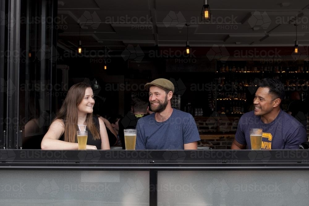 Three people sitting having a drink at a local craft beer bar - Australian Stock Image