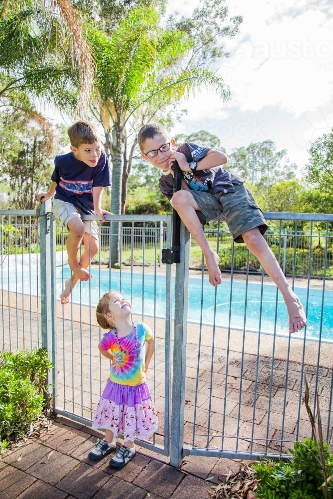 Image Of Three Siblings Climbing Over And Playing On Pool Fence