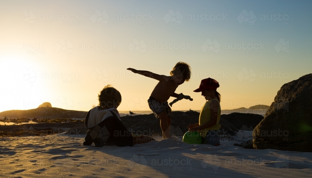 Three silhouette kids playing on the beach at sunset - Australian Stock Image