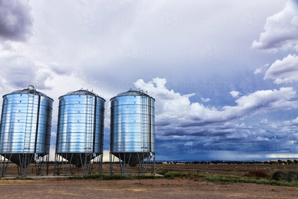 Three silos and farm land with storm clouds - Australian Stock Image