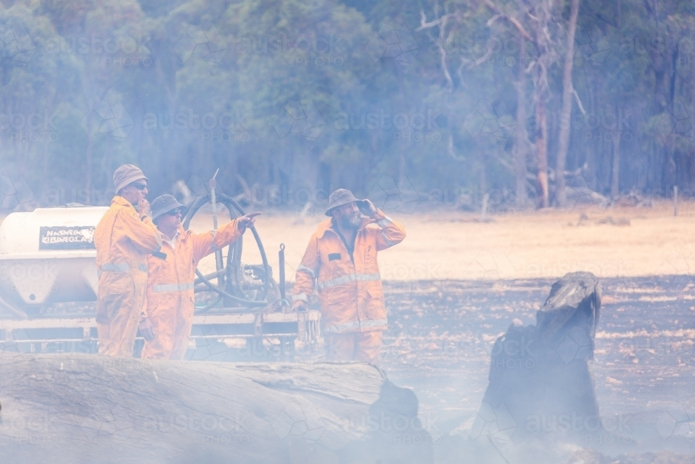Three volunteer firefighters in smoke surveying the damage after a fire - Australian Stock Image