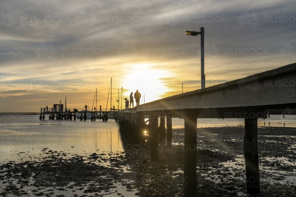 Timber jetty leading to sun setting through cloudy sky with people silhouettes - Australian Stock Image